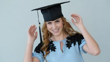 A female graduate smiling while wearing a graduation cap and a light blue dress with black accents.