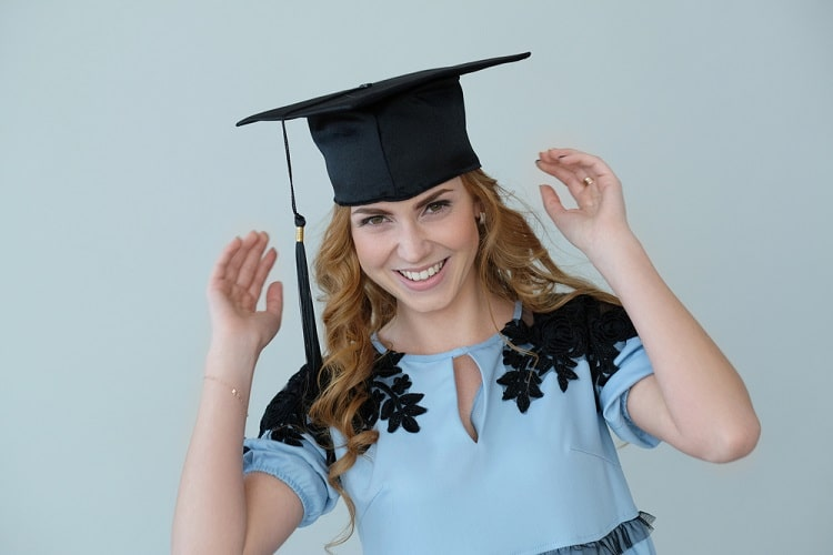 A female graduate smiling while wearing a graduation cap and a light blue dress with black shoulder accents.