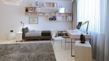 A minimalist-style dorm room with shelves above the bed for maximum storage and a large gray furry area rug in the middle to serve as an accent.