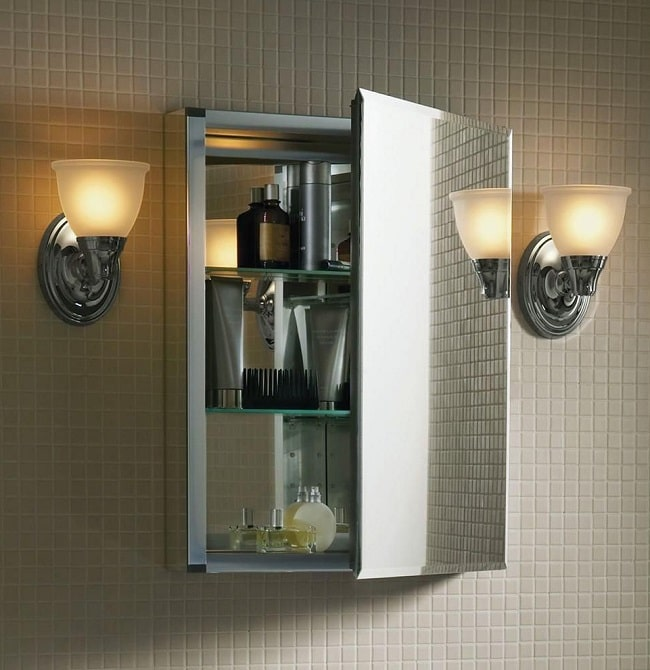 A square-shaped space-saving medicine cabinet installed on a bathroom wall with two warm lights on either side.