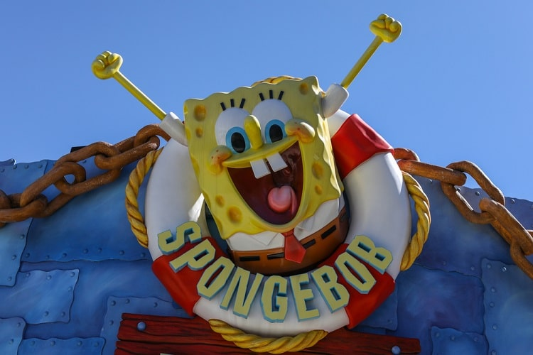 A photo of SpongeBob SquarePants with a life buoy around his body and his arms raised upward.