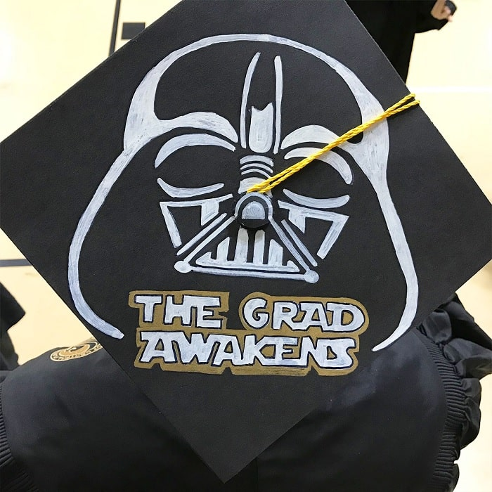 """A graduation cap inspired by Star Wars, with the words, """"The Grad Awakens"""" and a drawing of Darth Vader made using white fabric paint."""