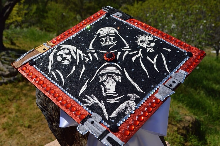 A graduation cap inspired by Star Wars, with drawings of characters from the dark side and the edges adorned with red rhinestones and glitter.
