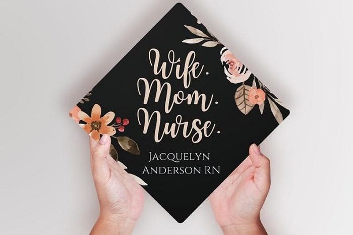 """A """"wife, mom, nurse"""" nursing graduation cap made of vinyl decal lettering, a black base, and floral print on the edges."""
