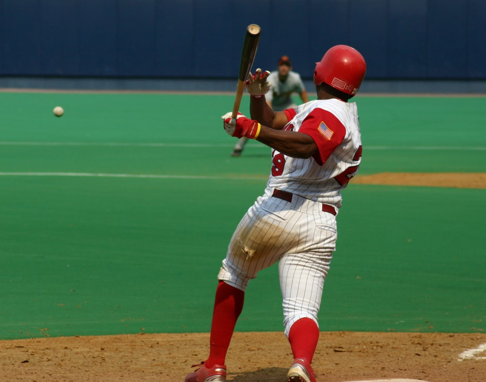 A baseball player batting during the first half inning during a college baseball game.