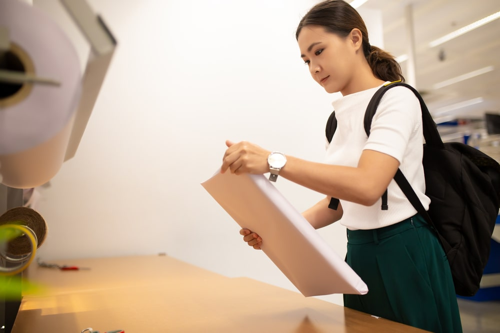 A female college student picking up her parcel from the school's central pickup location.