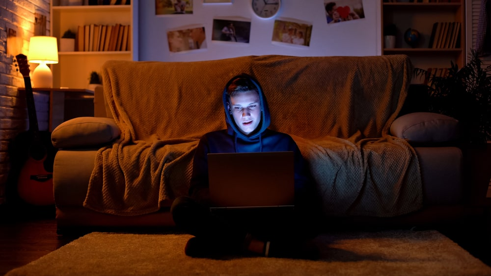 A college student wearing a dark-colored hoodie and surfing prohibited sites in the dark inside a college dorm room.