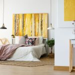 A college dorm room with a vibrant pink and gold motif, adorned with a pink throw blanket and yellow-gold wall accents.