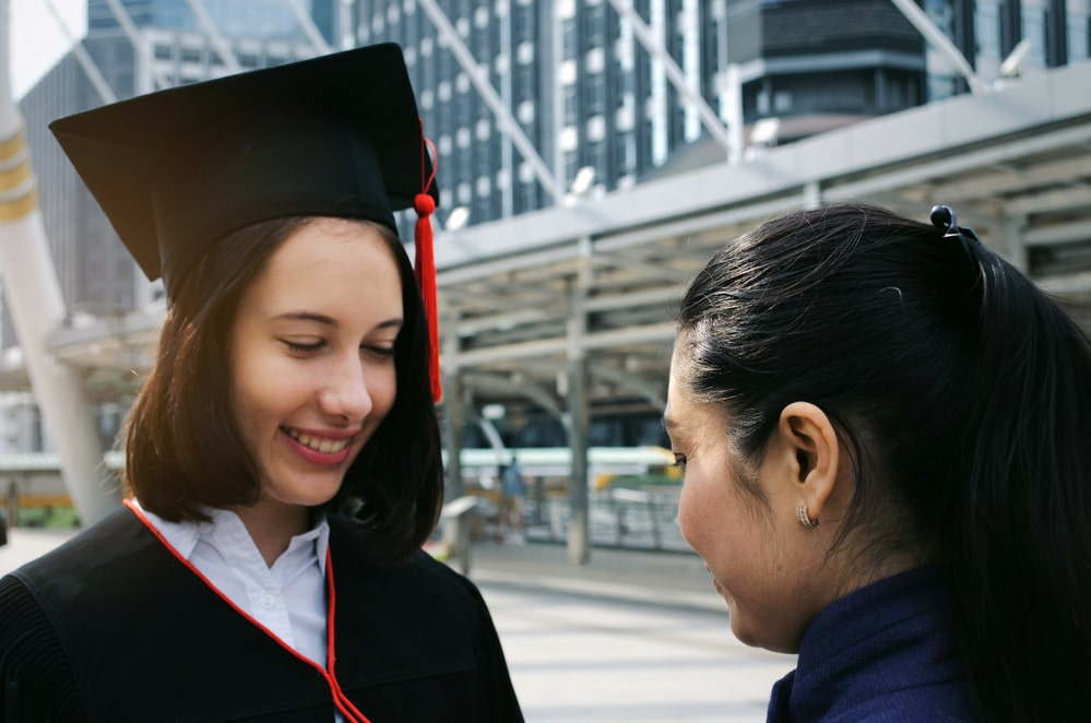 A girl congratulating her sister who's just graduated from college, right outside the graduate ceremony venue.