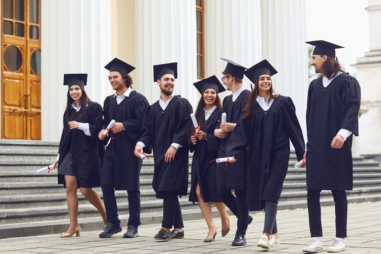 A group of college graduates wearing their caps and gowns and holding their diplomas while walking side by side outside a university building.