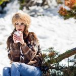A female college student holding a cup of hot beverage while enjoying the snowy mountains during winter break.