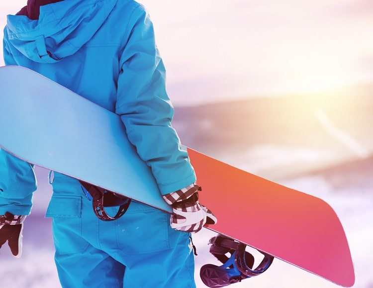 A college guy in snowboarding gear at a big mountain ski resort.