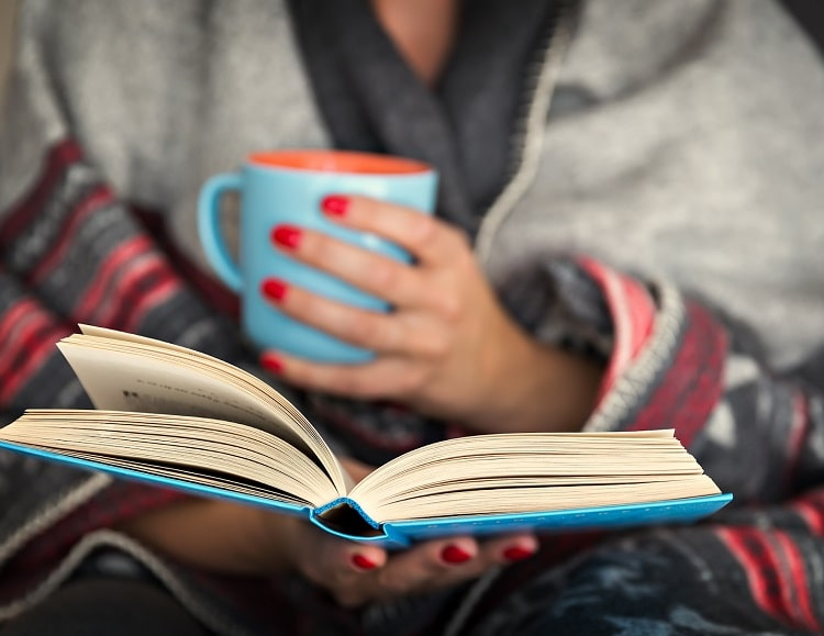 A college girl wearing winter clothes and holding a mug of hot beverage while doing some light reading.