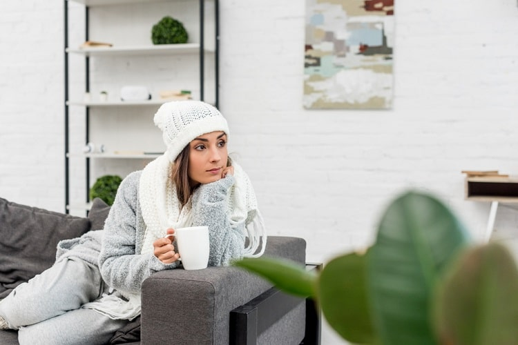 A college girl wearing winter clothes and holding a mug of hot beverage while sitting pensively on a couch in the living room.