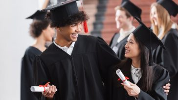 Two college graduates having an animated conversation after the ceremony, with other graduates in the background.