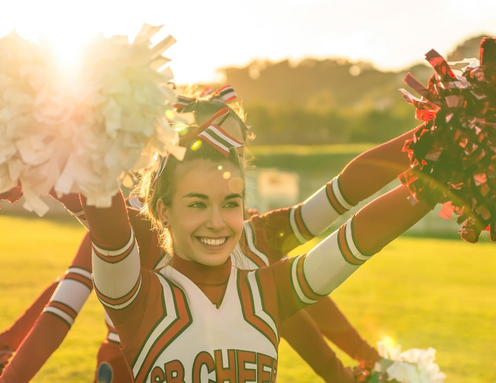 A college cheerleader practicing with her squad on the open field.