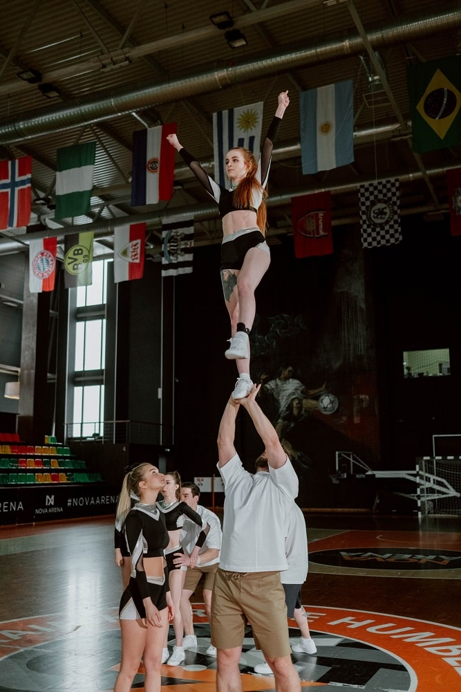A college female cheerleader being lifted up during cheer practice at an indoor court.
