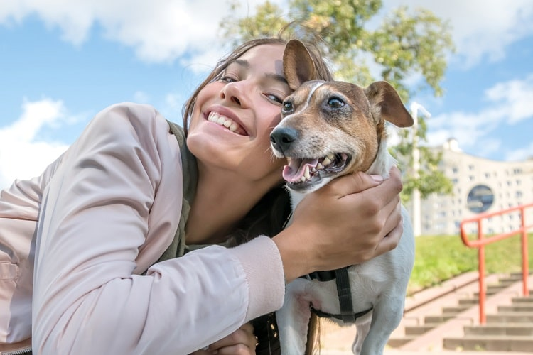 A college girl hugging her dog while posing outside a college building.