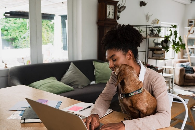 A female college student cradling her dog in her lap while studying in the living room.