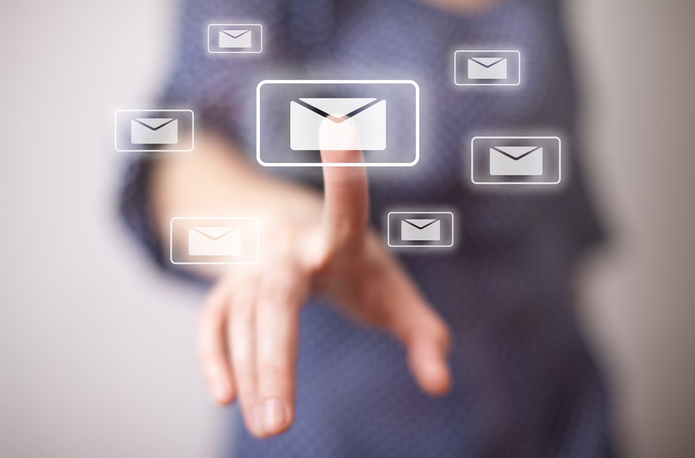 A hand with the index finger pressing on an email icon, along with other email icons surrounding it.