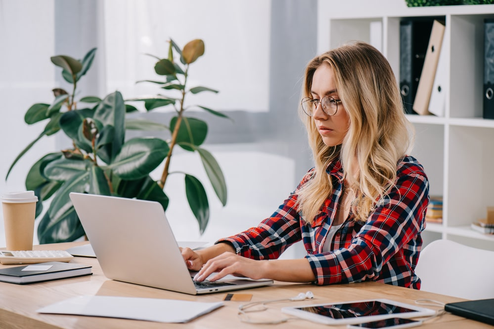 A female college graduate wearing a plaid shirt, checking her emails on her laptop at her work desk.