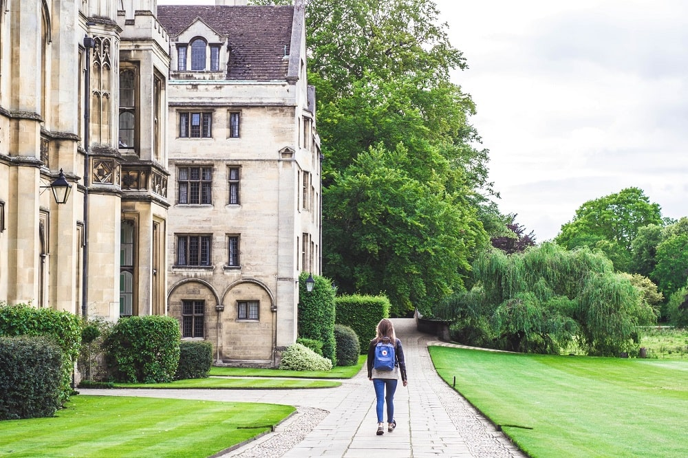 A girl wearing jeans and a backpack, walking along the university grounds, on her way to speak to the college admissions officer to decline her acceptance.