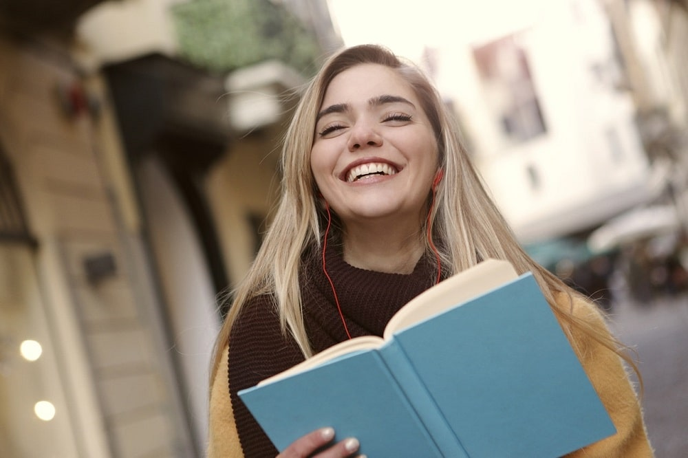 A college girl with her earphones on smiling while holding a library book.