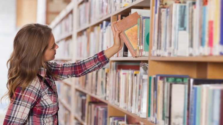 A female college student wearing a plaid shirt, browsing the fiction section of her college library.