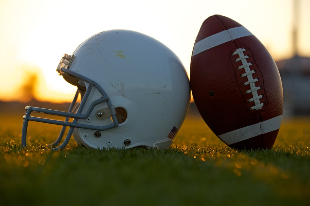 A football and a helmet placed on the grassy lawn of a college football field.