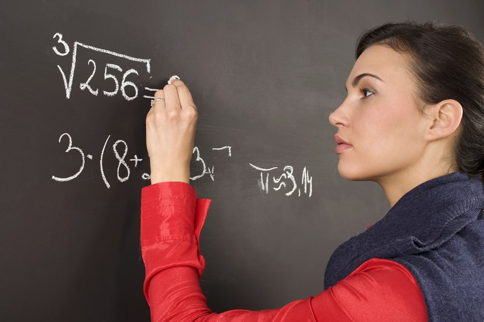 A college student solving a mathematical equation on the blackboard using white chalk.