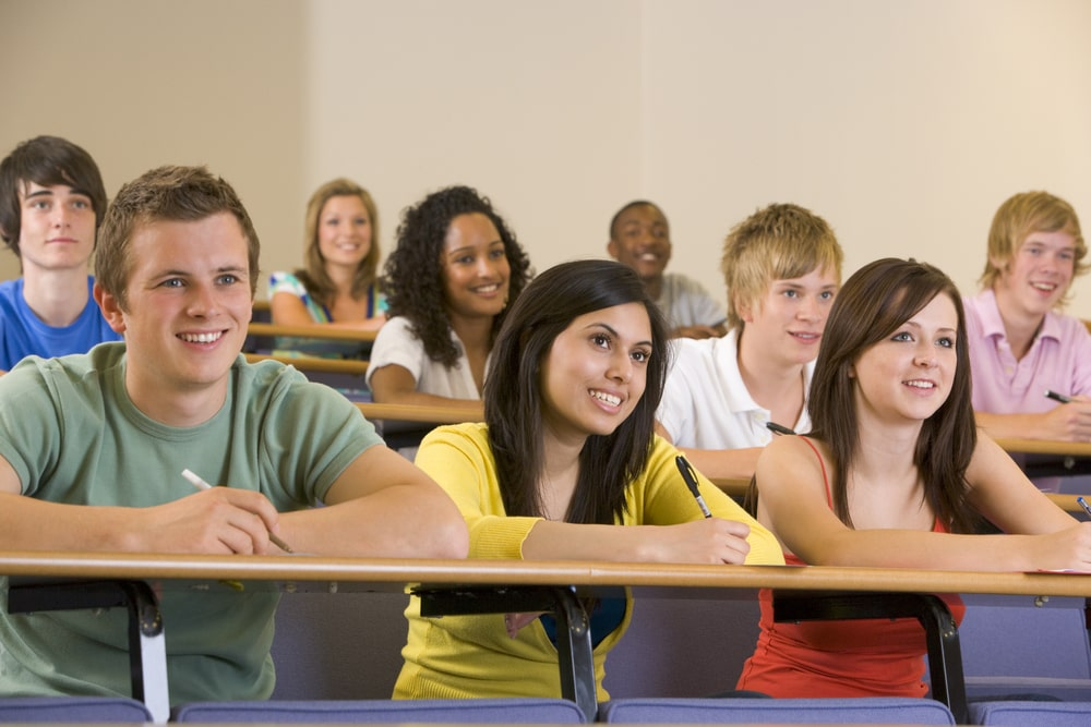 College freshmen smiling while listening to a university lecture of their professor inside a classroom.