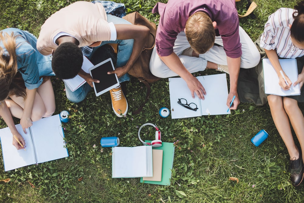 College students sitting on a grassy lawn, studying and multitasking to meet the demands of their week's schedule.