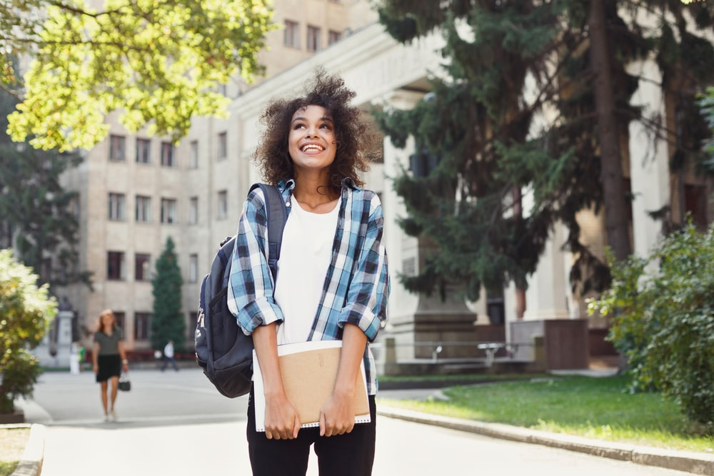 A college girl wearing a plaid shirt and holding her notebook, while smiling and looking around campus to see what college life has to offer.