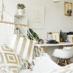 A dorm room hammock with white and gold throw pillow accents and a white throw blanket.