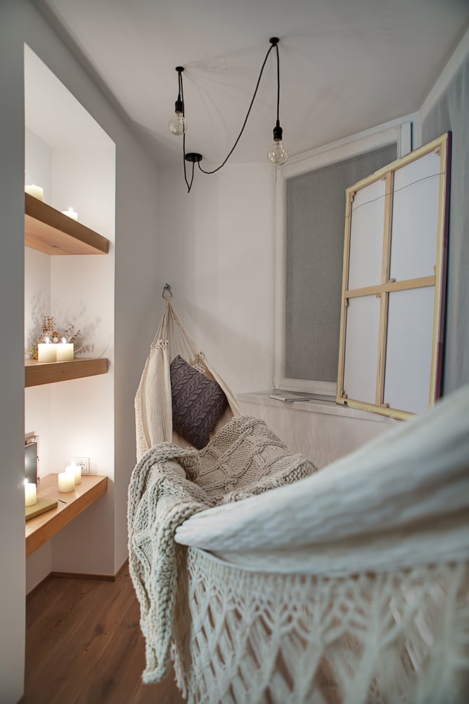 A dorm room wall hammock attached to the wall, with modern-style room accents.