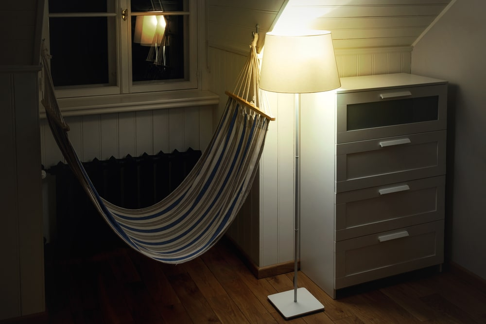 A dorm room hammock beside a lamp and hanging right by the window, properly installed with the right materials.