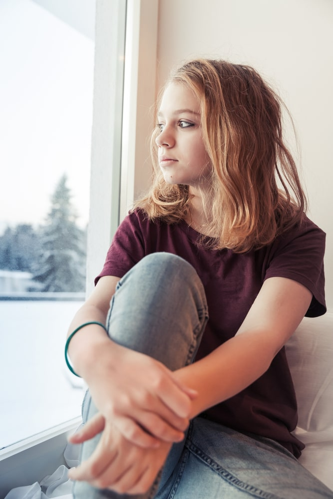 A college girl wearing a maroon shirt and denim pants, sitting by the window sill of her dorm room, looking out the window, and missing home.