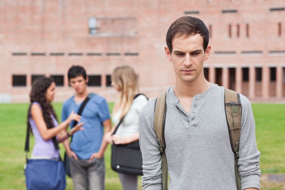 A college guy looking down on the ground and feeling lonely, while his classmates talk animatedly in the background, standing outside the university building.