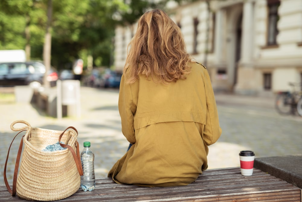A college girl wearing a mustard-colored jacket, sitting alone on the bench with her coffee on her right and her bag on her left, missing home.