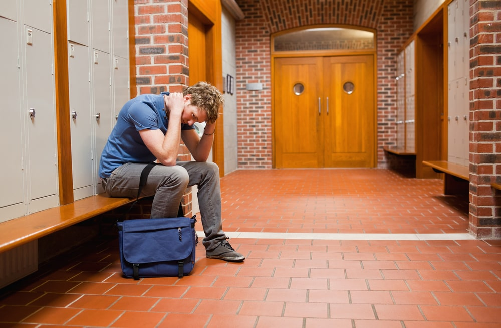Lonely college guy sitting in the hallway, head bent to the ground and hands on his head, trying to overcome his homesickness.