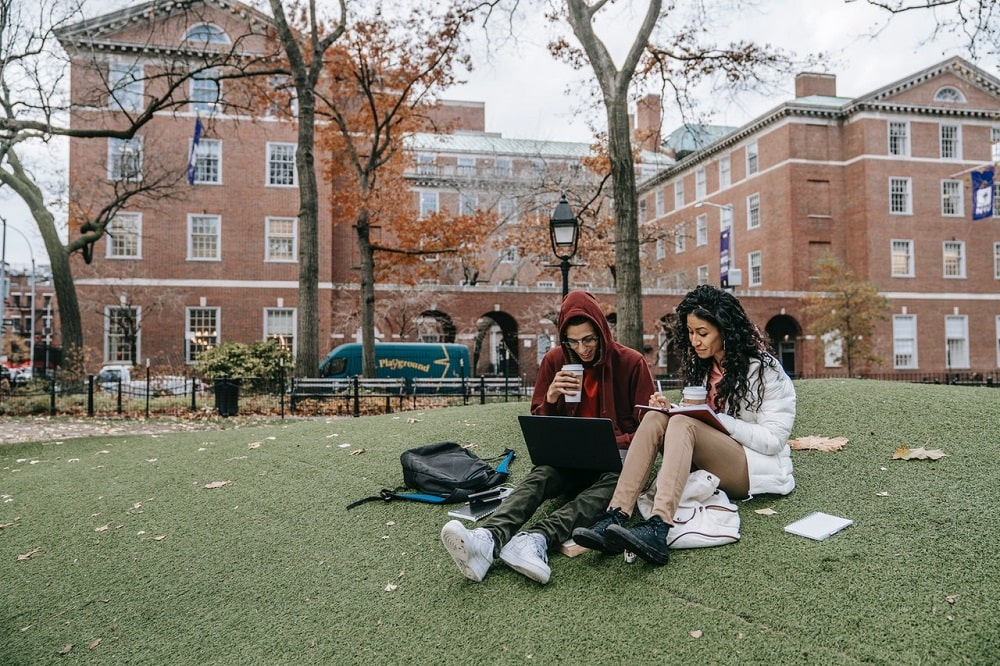 Two college friends sipping coffee while sitting on a grassy lawn outside the campus and working on their homework.