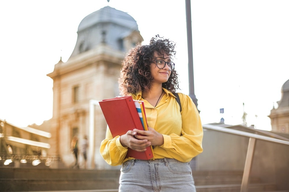 A college girl wearing glasses, a yellow top, and jeans, with books in hand, while standing outside the campus looking happy.
