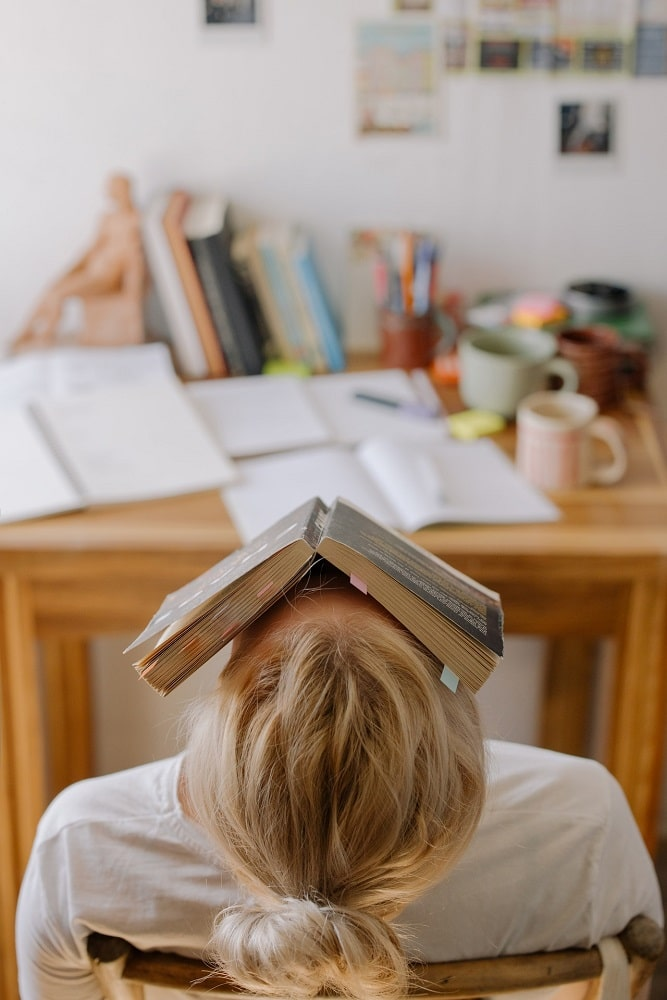 A college student with a book covering the face and homework lying on a wooden desk in a dorm room.