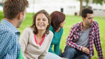 A group of college students conversing with each other while sitting on a grassy lawn outside the college building.