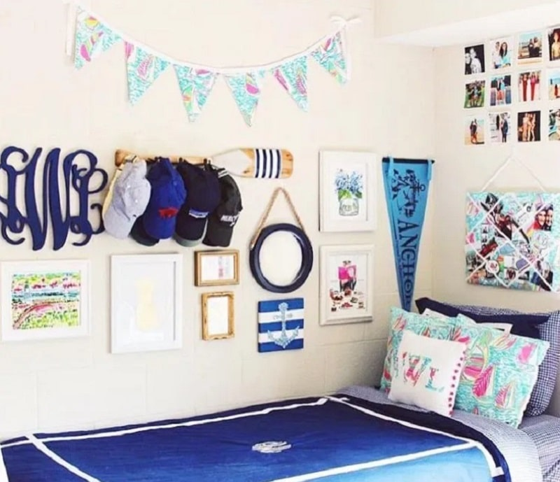 A nautical-themed college dorm room adorned with wooden wall art, flags, and boating-inspired decor.