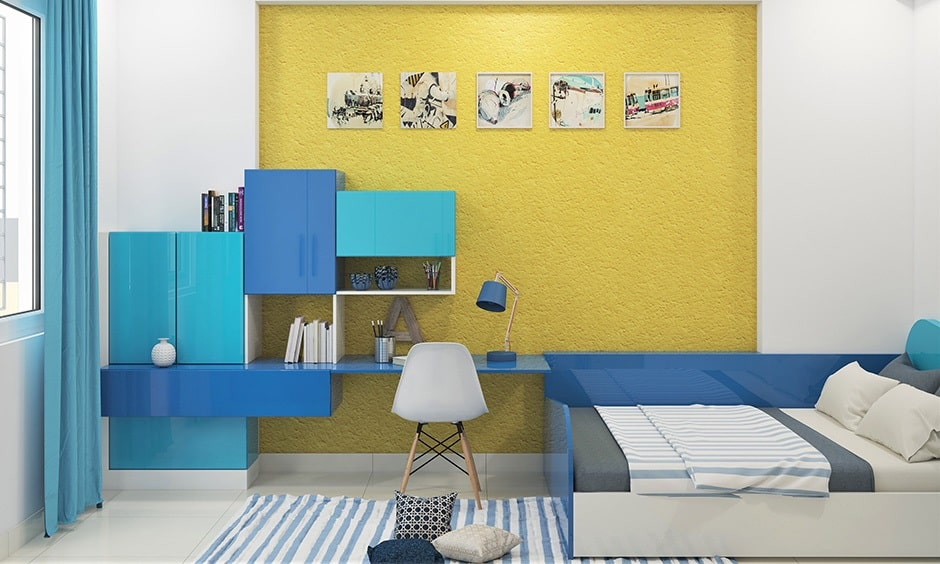 A college dorm room with a primary colors motif, the walls being adorned with yellow stick-on wallpaper, along with complementary blue cabinetry for the study corner.