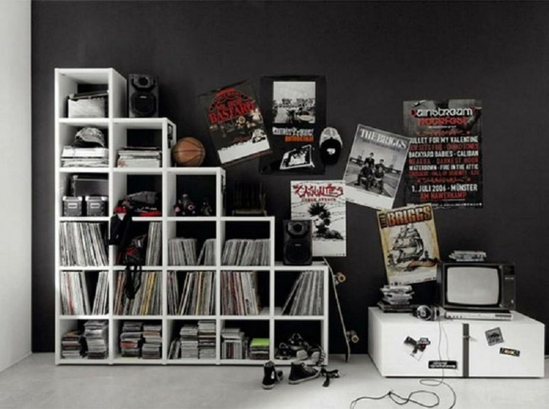 A punk rock-theme bedroom with a cube storage organizer and retro music album posters adorning the black wall.
