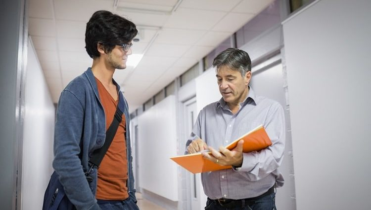 A college guy consulting his professor who's holding a large orange notebook while pointing to a page out in the hallway.