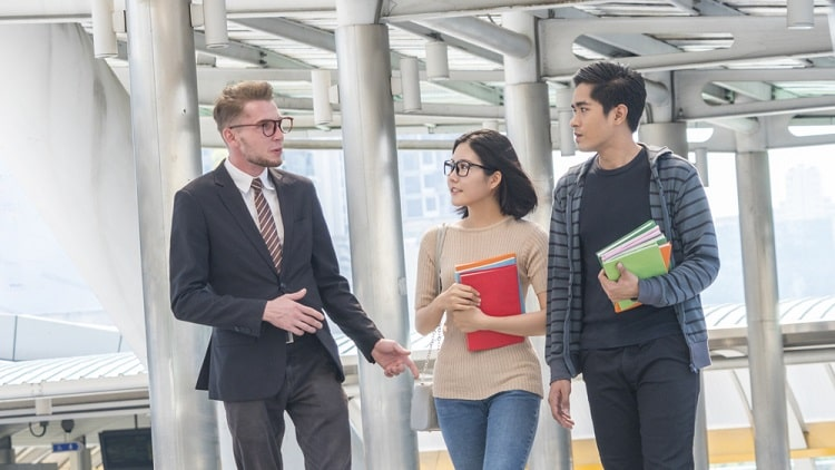 Two college students consulting their professor who's walking outside the university building.