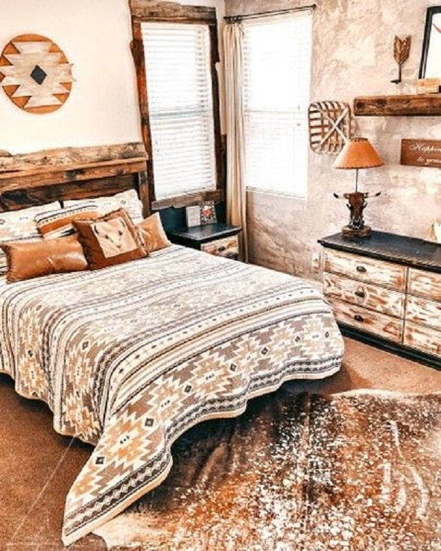 A southwest-style college dorm room adorned with Native American-themed beddings and a faux cowhide rug placed on the floor.
